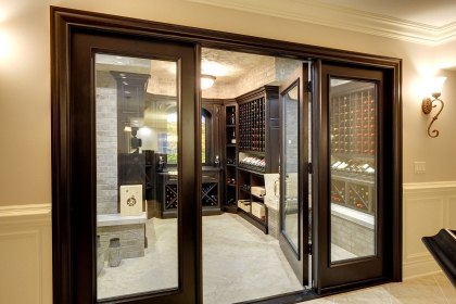 See-through, custom-made glass panel wine cellar entry system.