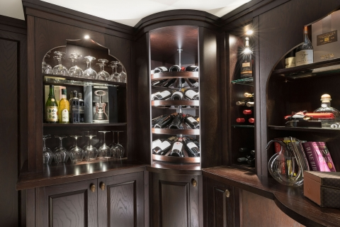 Second rotating wine cradles in between glass-and-wood shelving.