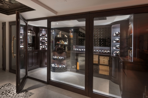 See-through custom glass panel wine cellar entry system showcasing furniture-grade solid wood.