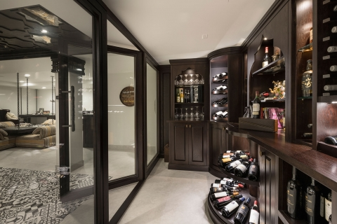 Side-view of wine cellar featuring custom glass and wood paneled entryway.