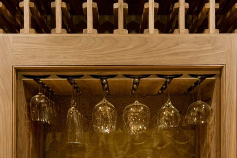 Functional and elegant custom glassware display in wine cellar.